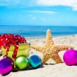 Starfish with gift box and christmas balls on the beach — Stock Photo