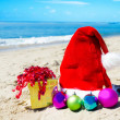 Christmas hat with gift box and christmas balls on the beach — Stock Photo #30780455