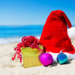 Christmas hat with gift box and christmas balls on the beach — Stock Photo #30780489