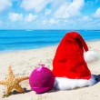 Christmas hat with christmas ball and starfish on the beach — Stock Photo