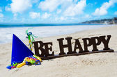 "Sign ""Be Happy"" with Birthday decorations on the beach — Stock Photo"