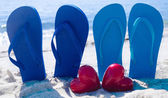 Flip flops with hearts on the beach — Stock Photo