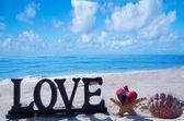 Signe « love » avec l'étoile de mer, coquillage et le coeur sur la plage — Photo