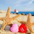 Starfishes with hearts on sandy beach — Stok Fotoğraf #39070003