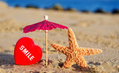 Starfish with heart on the sandy beach — Stock Photo