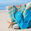 Beach bag with flip flops by ocean — Stock Photo #41240599