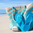 Beach bag with flip flops by ocean — Stock Photo #41240607