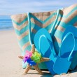 Beach bag with flip flops by ocean — Stock Photo #41240639
