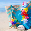 Beach bag with flip flops by ocean — Stock Photo #41240691