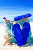 Beach bag with flip flops by the ocean — Stock Photo