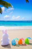 Easter bunny and color eggs on the beach — Stock Photo