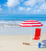 Beach umbrella and chair by the ocean — Stock Photo
