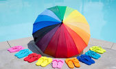Color umbrella and flip flops by the pool — Stock Photo