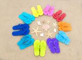 Color flip flops on sandy beach — Stock Photo