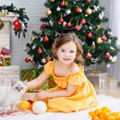 Little girl with a cat in a holiday room — Stock Photo