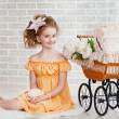 Girl in orange dress with vintage pram — Stock Photo