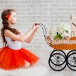 Girl in orange skirt with vintage pram — Stock Photo