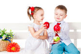 Boy and girl sitting on a bench with red apples — Stock Photo