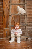 Little girl with a cat on a porch — Stock Photo