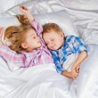 Happy little boy and girl in bed — Stock Photo #26074235