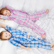 Two merry children playing on the bed — Stock Photo