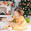 Stock Photo: Little girl with cat in holiday room