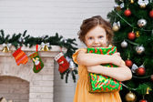 Little girl with a gift near the Christmas tree — Stock Photo