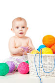 Smiling baby plays with colored balls of yarn — Stock Photo