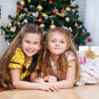 Two little girls near the Christmas tree with gifts — Stock Photo #26909709