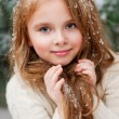 Beautiful little girl catches snowflakes — Stock Photo