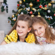Two little girls near the Christmas tree with gifts — Stock fotografie