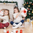 Two little girls in a room with Christmas gifts — Stock Photo