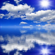 The sun,the clouds in the blue sky reflected in the water — Stock Photo