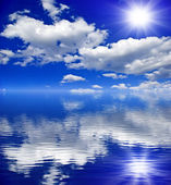 The sun,the clouds in the blue sky reflected in the water — Foto de Stock