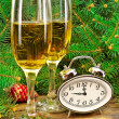 Wine glasses, watches, Christmas toys, near  New Year tree. — Stock Photo