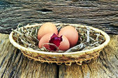 Eggs,a precious stone in the egg,placed in a basket on the wooden background — Stock Photo