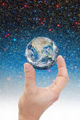 Hand holding planet earth in space — Stock Photo