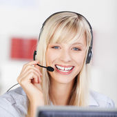 Friendly businesswoman wearing a headset — Stock Photo