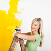 Smiling female painting yellow — Stock Photo