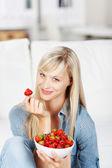 Woman enjoying a bowl of strawberries — Stock Photo