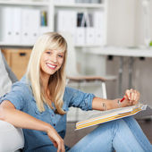 Smiling woman with folder at home — Stock Photo