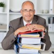 Relaxed businessman with a stack of binders — Stock Photo