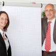 Two colleagues standing next to white flipchart — Stock Photo #25825527