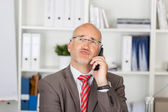 Businessman Puckering Lips While Using Cordless Phone — Stock Photo