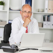 Reliable businessman with hand on chin — Stock Photo