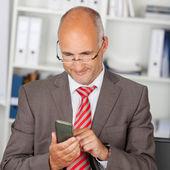 Biznesmen korzystanie smartphone w biurze — Zdjęcie stockowe