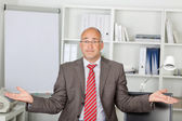 Businessman Shrugging Shoulders In Office — Stock Photo