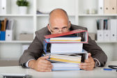 Businessman looking over a stack of binders — Photo