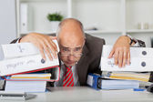 Overworked Businessman Leaning On Stack Of Binders — Stockfoto
