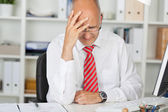 Upset Businessman With Hand On Head At Desk — Stock Photo